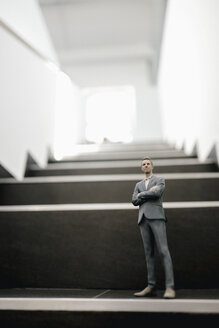 Businessman figurine standing on stairs in office - FLAF00098