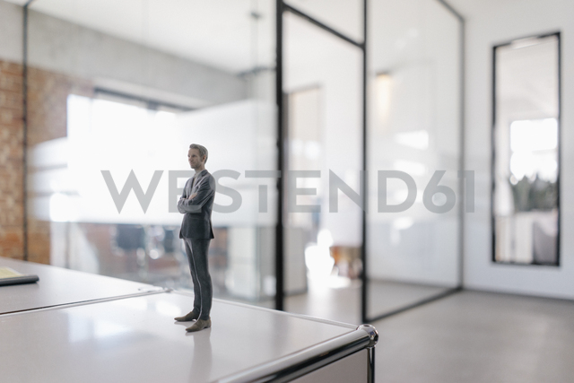 Businessman figurine standing on desk in modern office - FLAF00104