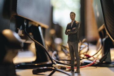 Businessman figurine standing amidst computer cables - FLAF00107