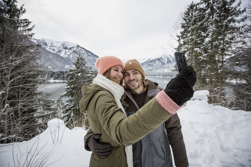 Smiling couple taking a selfie in alpine winter landscape with lake - SUF00398