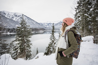 Young woman standing in alpine winter landscape with lake - SUF00401