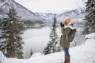Young woman with hot drink standing in alpine winter landscape with lake - SUF00404