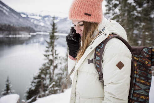 Young woman on cell phone in alpine winter landscape with lake - SUF00410