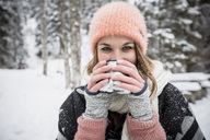 Portrait of young woman drinking hot drink outdoors in winter - SUF00416