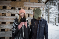 Portrait of happy couple in front of wood pile outdoors in winter - SUF00419