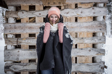Portrait of smiling young woman in front of wood pile outdoors in winter - SUF00422