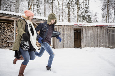 Happy couple running in front of wood pile outdoors in winter - SUF00425