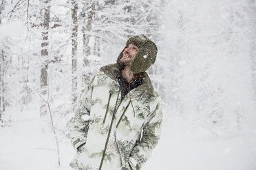 Happy man in camouflage jacket in winter forest - SUF00428