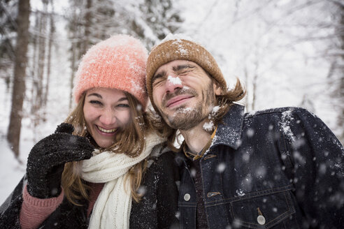 Happy couple having fun with snow in winter landscape - SUF00437