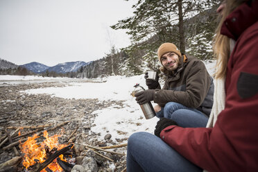 Couple on a trip in winter having a hot drink at camp fire - SUF00446