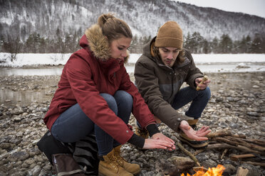 Couple on a trip in winter warming hands at camp fire - SUF00449
