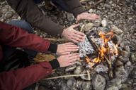 Close-up of couple warming hands at camp fire - SUF00452