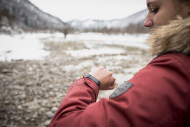 Young woman with smartwatch in winter - SUF00455