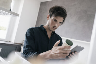 Portrait of young man using tablet for getting information of a product - KNSF03423