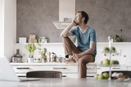 Smilingg man sitting on kitchen counter looking at distance - KNSF03444