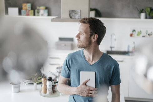 Man with tablet standing in the kitchen looking at distance - KNSF03453