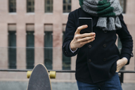 Man with cell phone and skateboard in the city, partial view - JRFF01493