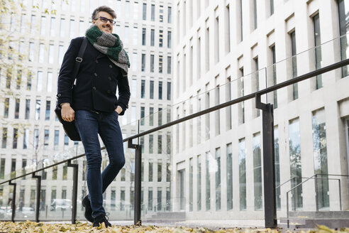 Content businessman walking in the city in autumn - JRFF01502