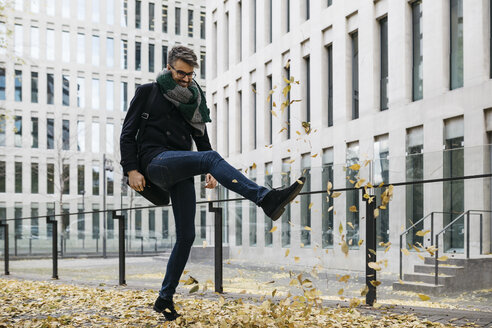 Businessman playing with autumn leaves in the city - JRFF01505