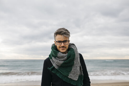 Portrait of man on the beach wearing knitted scarf - JRFF01508