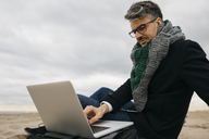 Businessman sitting on the beach in winter using laptop - JRFF01514