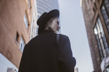 Woman with hat dressed in black walking in the city - KMKF00134