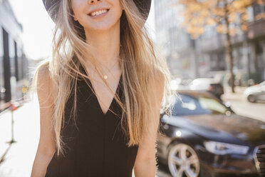 Laughing blond woman dressed in black walking in the city, partial view - KMKF00137