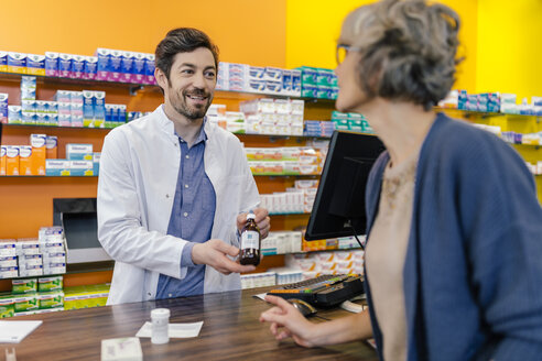 Pharmacist explaining medicine to customer in pharmacy - MFF04278