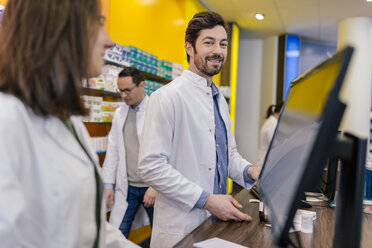 Portrait of smiling pharmacist with colleagues at counter in pharmacy - MFF04281