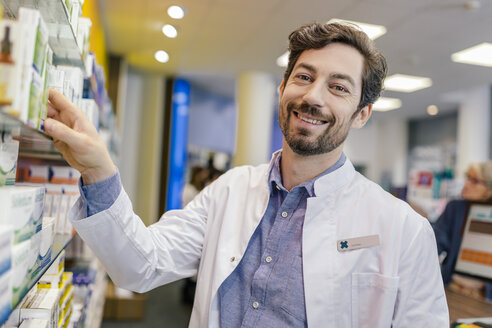 Portrait of smiling pharmacist with medicine at shelf in pharmacy - MFF04284