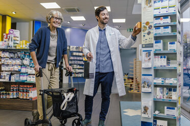 Smiling pharmacist and customer with wheeled walker in pharmacy - MFF04287