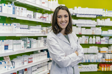 Portrait of smiling pharmacist at shelf with medicine in pharmacy - MFF04290