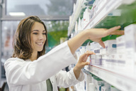 Smiling pharmacist sorting medicine at shelf in pharmacy - MFF04296
