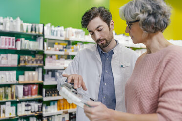 Pharmacist advising customer with sclaes in pharmacy - MFF04302