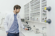 Smiling man with microscope in laboratory - MFF04311