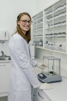 Portrait of smiling woman using scales in laboratory of a pharmacy - MFF04314