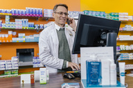 Smiling pharmacist talking on phone at counter in pharmacy - MFF04320