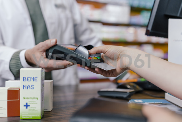 Close-up of customer paying cashless in a pharmacy - MFF04323