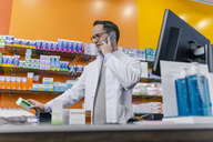 Pharmacist talking on phone at counter in pharmacy - MFF04329