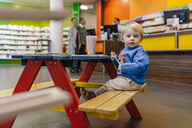 Little boy sitting on bench in pharmacy with parents in background - MFF04338