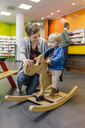Little boy and mother playing with rocking horse in pharmacy - MFF04341
