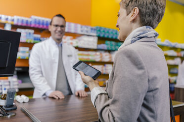 Smiling woman with cell phone at counter in pharmacy - MFF04344
