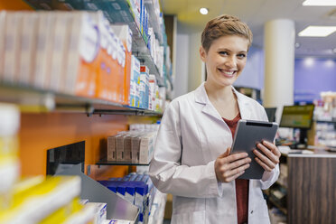 Portrait of smiling pharmacist at shelf with medicine in pharmacy holding tablet - MFF04347