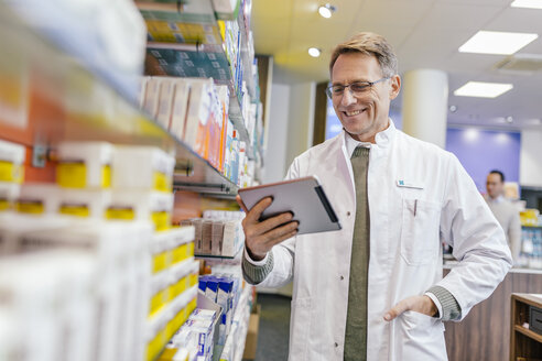 Smiling pharmacist at shelf with medicine in pharmacy holding tablet - MFF04350