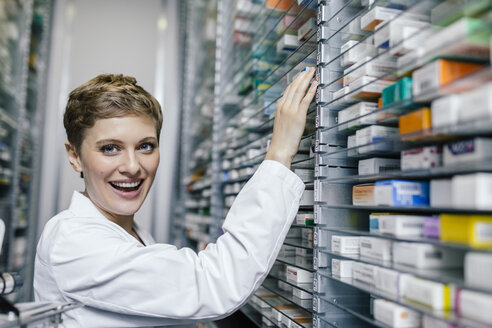 Smiling pharmacist sorting medicine at shelf in pharmacy - MFF04356