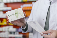 Pharmacist holding tablet package and prescription in pharmacy - MFF04365