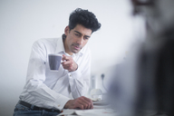 Portrait of businessman drinking coffee while reading newspaper in the morning at home - SGF02139