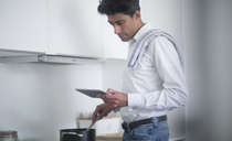 Man standing in kitchen reading news on his digital tablet while cooking - SGF02142
