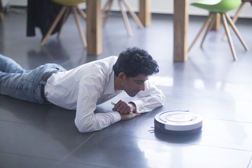 Man lying on the floor looking at robotic vacuum cleaner - SGF02145
