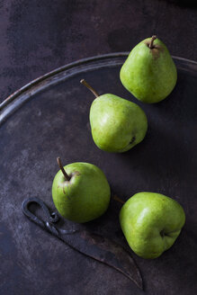Four green pears 'Alexander Lucas' and an old knife on rusty ground - CSF28688